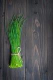Groupe de ciboulette fraîche sur une planche à découper en bois, foyer sélectif Images stock