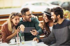 Groupe de cinq amis ayant un café ensemble Photo stock