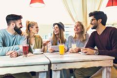 Groupe de cinq amis ayant un café ensemble Photographie stock
