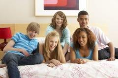 Groupe de cinq amis d'adolescent traînant dans Bedro Photographie stock