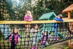 Groupe de cinq amis féminins d'école jouant sur le terrain de jeu Photo stock