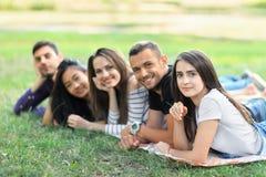 Groupe de cinq amis se situant dans la rangée en parc Photographie stock
