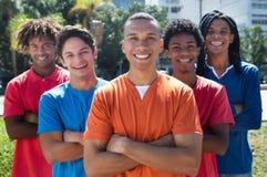 Groupe de cinq jeunes hommes avec les bras croisés Photos libres de droits