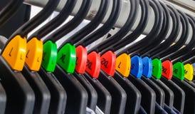 Groupe de cintre de tissu avec le divers label de classement par taille de couleur Image libre de droits