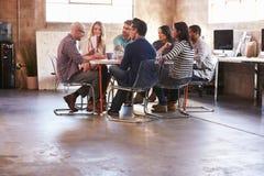 Groupe de concepteurs ayant la réunion autour du Tableau dans le bureau images stock