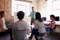 Groupe de concepteurs ayant la session de séance de réflexion dans le bureau photos libres de droits