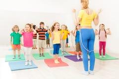 Groupe de cordes à sauter d'enfants heureux à la leçon de gymnase Photo libre de droits