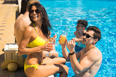 Groupe de couples gais buvant des cocktails dans la piscine Photo stock