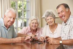 Groupe de couples supérieurs appréciant le jeu des dominos à la maison Image stock
