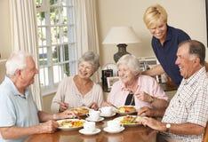 Groupe de couples supérieurs appréciant le repas ensemble dans la maison de soin avec l'aide familiale Images stock
