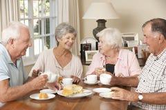 Groupe de couples supérieurs appréciant le thé d'après-midi ensemble à la maison Photographie stock libre de droits