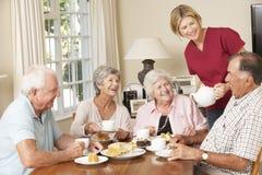 Groupe de couples supérieurs appréciant le thé d'après-midi ensemble à la maison avec l'aide familiale Photographie stock libre de droits