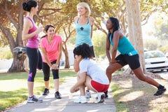 Groupe de coureurs féminins réchauffant avant course Photographie stock libre de droits