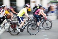 Groupe de cyclistes dans la ville dans la tache floue de mouvement Images stock