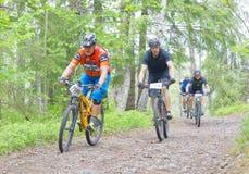 Groupe de cyclistes de vélo de montagne dans la forêt faisant un cycle en descendant Image libre de droits