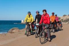 Groupe de cyclistes montant le vélo de montagne de plage sablonneuse avec le sac à dos Photos stock