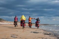 Groupe de cyclistes montant le vélo de plage sablonneuse Photo stock