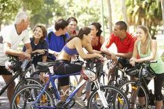 Groupe de cyclistes se reposant pendant le tour de cycle par le parc Images libres de droits