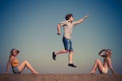 Groupe de détente de filles du garçon deux d'amis extérieure Photographie stock