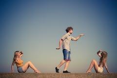 Groupe de détente de filles du garçon deux d'amis extérieure Image stock