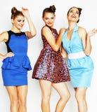 Groupe de dames élégantes diverses dans des robes lumineuses d'isolement sur le blanc souriant ayant l'amusement, concept de pers Photographie stock