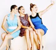 Groupe de dames élégantes diverses dans des robes lumineuses d'isolement sur le blanc souriant ayant l'amusement, concept de pers Photos stock