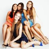 Groupe de dames élégantes diverses dans des robes lumineuses d'isolement sur le blanc souriant ayant l'amusement, selfie de obser Photographie stock