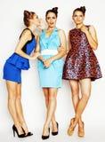Groupe de dames élégantes diverses dans des robes lumineuses d'isolement sur le blanc souriant ayant l'amusement, selfie de obser Photographie stock libre de droits