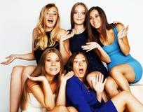 Groupe de dames élégantes diverses dans des robes lumineuses sur le blanc souriant ayant l'amusement, selfie de observation, mode Photo stock
