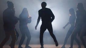 Groupe de danseurs de rue effectuant différents mouvements sur la rue sombre banque de vidéos