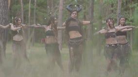 Groupe de danseuses de femmes avec le maquillage et dans des costumes fabuleux mystiques dansant la danse routinière dans la fumé banque de vidéos