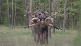Groupe de danseuses de femmes avec le maquillage et dans des costumes fabuleux mystiques dansant la danse routinière dans la fumé clips vidéos