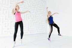 Groupe de deux femmes convenables de jeunes ayant l'amusement tout en dansant Photo stock