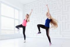 Groupe de deux jeunes femmes convenables ayant une classe de danse de forme physique Image stock