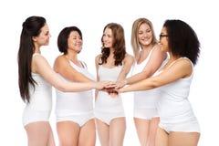 Groupe de différentes femmes heureuses avec des mains sur le dessus Photos libres de droits