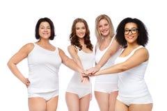Groupe de différentes femmes heureuses avec des mains sur le dessus Photo libre de droits