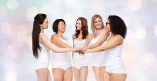 Groupe de différentes femmes heureuses avec des mains sur le dessus Images libres de droits