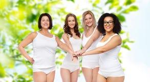 Groupe de différentes femmes heureuses avec des mains sur le dessus Photo stock