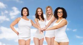 Groupe de différentes femmes heureuses avec des mains sur le dessus Image libre de droits
