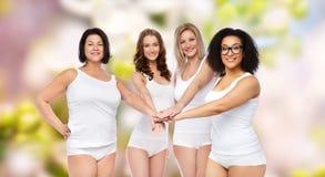 Groupe de différentes femmes heureuses avec des mains sur le dessus Image stock