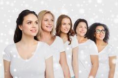 Groupe de différentes femmes heureuses dans des T-shirts blancs Photo stock
