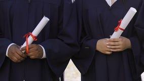 Groupe de diplômés multi-ethniques tenant des diplômes d'études secondaires dans des mains, égalité banque de vidéos