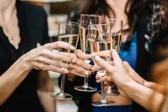 Groupe de faire la fête des filles faisant tinter des cannelures avec le vin mousseux Photo stock