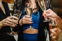 Groupe de faire la fête des filles faisant tinter des cannelures avec le vin mousseux Image stock