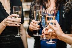 Groupe de faire la fête des filles faisant tinter des cannelures avec le vin mousseux Photos stock