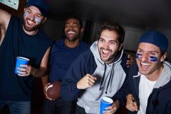 Groupe de fans de sports masculins observant le jeu à la télévision Images stock