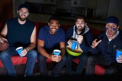 Groupe de fans de sports masculins observant le jeu à la télévision Photos stock