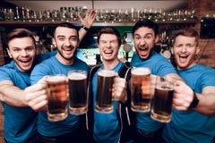 Groupe de fans de sports buvant de la bière célébrant et encourageant à la barre de sports Photos libres de droits