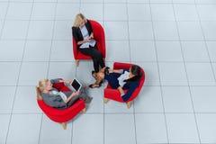Groupe de femme d'affaires s'asseyant dans des fauteuils utilisant des instruments causant la vue d'angle supérieur en ligne Image libre de droits