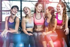 Groupe de femme d'ajustement souriant tout en se reposant sur des boules d'exercice Photos stock